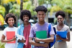 Afrikanischer männlicher Student mit Gruppe Afroamerikanerstudenten lizenzfreie stockfotografie