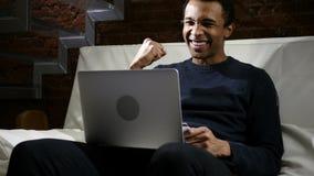 Afrikanischer Mann aufgeregt für das erfolgreiche on-line-Einkaufen stockbild