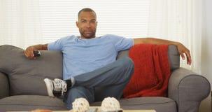 Afrikanischer Mann, der auf der Couch fernsieht sitzt Stockfotos