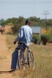 Afrikanischer Mann, der auf Fahrrad sich lehnt Lizenzfreies Stockbild