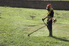 Afrikanischer Mann, der den Rasen schneidet stockbilder