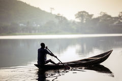 Afrikanischer Mann, der ein Kanu reitet Lizenzfreies Stockfoto