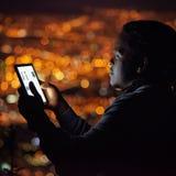 Afrikanischer Mann, der eine Tablette nachts mit Stadtbildhintergrund verwendet Lizenzfreie Stockfotos