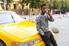 Afrikanischer Mann, der einen Kaffee gesetzt auf der Haube eines Taxis, schauend zu einer Seite, auf einem Stra?enhintergrund tri lizenzfreie stockfotos
