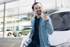Afrikanischer Mann, der einen Schlüssel nahe seinem Auto spielt Stockfoto