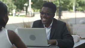 Afrikanischer Mann, der Geschäftsstrategie seinem afrikanischen weiblichen Kollegen, unter Verwendung des Laptops während der Sit stock video footage