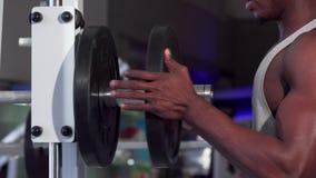 Afrikanischer Mann, der Gewichtsplatten auf den Barbell, trainierend an der Turnhalle setzt stock footage