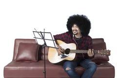 Afrikanischer Mann, der Gitarre und hörende Musik spielt Stockfotos