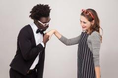 Afrikanischer Mann, der Handkaukasische Frau und sie lächelnd küsst Stockbilder