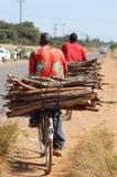 Afrikanischer Mann, der Holz transportiert Stockbild