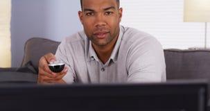 Afrikanischer Mann, der im Fernsehen durch Kanäle leicht schlägt Lizenzfreie Stockbilder