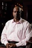 Afrikanischer Mann, der im Stuhl sitzt Stockfotografie