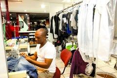 Afrikanischer Mann, der Kleidung an einer chemischen Reinigung repariert stockbild