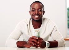 Afrikanischer Mann, der US-Dollars hält Stockfotos