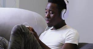 Afrikanischer Mann, der zu Hause Musik in den Kopfhörern, Ton genießend hört stock video footage