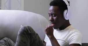 Afrikanischer Mann, der zu Hause Musik in den Kopfhörern, Ton genießend hört stock footage