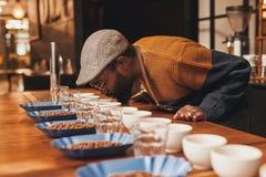 Afrikanischer Mann an einem Kaffeeprobieren, welches das Aroma nimmt stockfotos