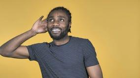 Afrikanischer Mann-hörende geheime Stellung lokalisiert auf gelbem Hintergrund stock video