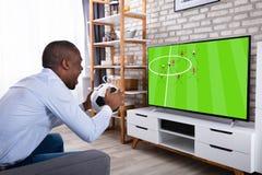 Afrikanischer Mann-Holding-Ball-aufpassendes Fernsehen lizenzfreie stockbilder