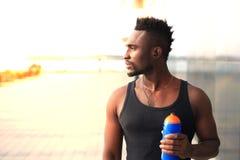 Afrikanischer Mann in Trinkwasser der Sportkleidungs bei, bei Sonnenuntergang oder Sonnenaufgang draußen stehen läufer lizenzfreies stockfoto