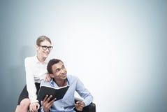 Afrikanischer Mann und blonde Frau im Lehnsessel, grau Stockbilder