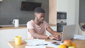 Afrikanischer Mann unter Verwendung des Laptops während kaukasische Freundinstellung einsam an der Küche stock footage