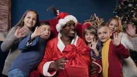 Afrikanischer Mann in Weihnachtsmann-Kostüm und in netten Kindern, die zur Kamera wellenartig bewegen stock video