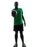 Afrikanischer Mannfußballspieler, der Fußballschattenbild zeigend hoding ist Stockbild