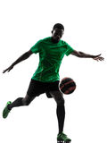 Afrikanischer Mannfußballspieler, der Schattenbild tritt Stockfotos