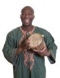 Afrikanischer Musiker mit traditioneller Kleidung und Trommeln lizenzfreie stockfotos