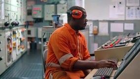 Afrikanischer Schiffsingenieuroffizier in Maschinenleitstelle ECR stock video footage