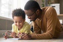 Afrikanischer Vati und wenig Kleinkindsohnabgehobener betrag mit farbigen Bleistiften lizenzfreie stockbilder