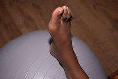 Afrikanischer weiblicher Fuß auf einem grauen Yogaball Stockbilder