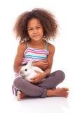 Afrikanisches asiatisches Mädchen, das ein Kaninchen anhält Lizenzfreies Stockfoto