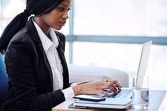 Afrikanisches beschäftigtes Arbeiten der Geschäftsfrau in einem Firmenkundengeschäftaufenthaltsraum Stockfotos
