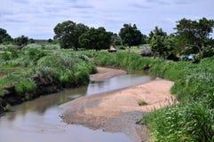Afrikanisches Dorf auf Flussufer Lizenzfreies Stockbild