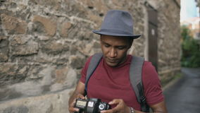 Afrikanisches glückliches touristisches nehmendes Foto auf seiner dslr Kamera Junger Mann, der in Europa reist stock video