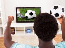 Afrikanisches junger Mann-aufpassendes Fernsehen, das Fußball hält Stockbild