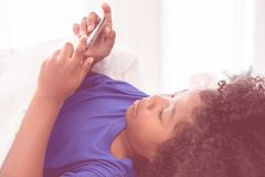Afrikanisches Kind spielt mit Smartphone auf Bett stockfotografie
