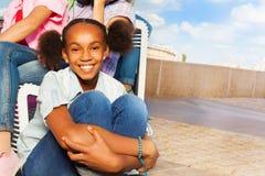 Afrikanisches lächelndes Mädchen, das auf entsteinter Straße sitzt Stockbild