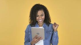 Afrikanisches Mädchen aufgeregt für Erfolg während unter Verwendung des Tablets lokalisiert auf gelbem Hintergrund stock video