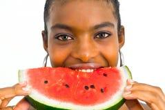Afrikanisches Mädchen, das eine Wassermelone isst Lizenzfreies Stockbild