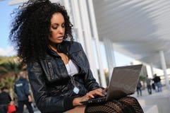 Afrikanisches Mädchen, das einen Laptop in der Straße verwendet Stockfotos