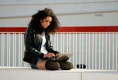Afrikanisches Mädchen, das einen Laptop in der Straße verwendet Stockfoto