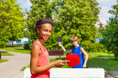Afrikanisches Mädchen, das Klingeln pong mit Jungen draußen spielt Lizenzfreies Stockbild
