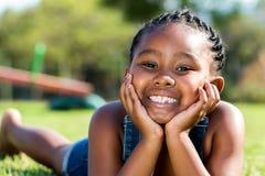 Afrikanisches Mädchen, das mit Gesicht auf Hände im Park legt Lizenzfreie Stockfotografie