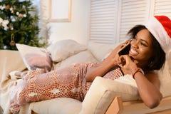 Afrikanisches Mädchen der Junge recht, das auf dem Sofa liegt und am Telefon nahe dem Weihnachtsbaum spricht lizenzfreies stockfoto