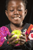 Afrikanisches Mädchen mit einem Apfel Lizenzfreies Stockfoto