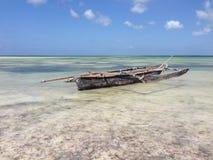Afrikanisches traditionelles altes Boot am Ozeanufer unter dem blauen Himmel Stockfoto