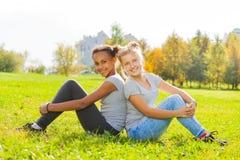 Afrikanisches und blondes Mädchen, das zusammen auf Gras sitzt Stockfoto